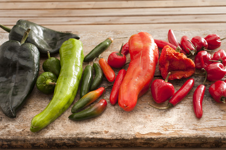 displayed: Large selection of fresh chili peppers of different varieties and colors displayed on a wooden kitchen counter, used as a pungent spice in cooking