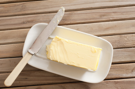 Pat of fresh farm butter on a butter dish with a knife to use as a spread or cooing ingredient, overhead view on a slatted wooden table Foto de archivo