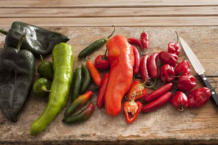 cut up: Variety of different chili peppers in a kitchen lying displayed by color on a wooden counter top with a knife waiting to be cut up for cooking