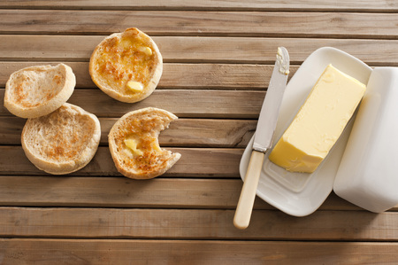 pat: Freshly baked and toasted tasty crumpets, one bitten into, on a wooden table with a pat of butter on a plate, overhead view