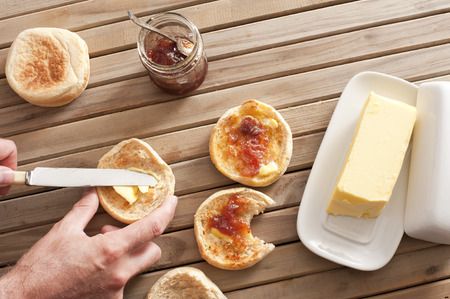 pat: Man buttering a freshly baked toasted crumpet for breakfast from a large pat of butter with a jar of preserve or jam alongside, overhead view of his hands Stock Photo