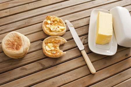 buttered: Buttered crumpets, one bitten into, with a pat of farm butter on a wooden slatted table, high angle view