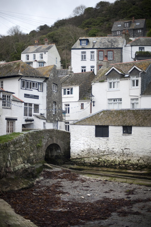 Desolate Polperro fishing village in Cornwall with little stream and stone bridge near bottom of hill next to buildings