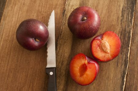 pip: Fresh whole and halved plums showing the stone or pip lying on a wooden table with a knife in a close up overhead view Stock Photo