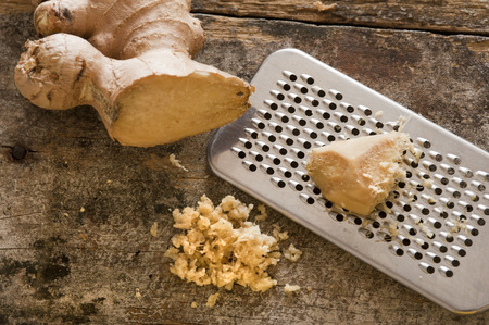 Fresh ginger root, shavings and stainless steel grater over old worn out wooden table Banco de Imagens