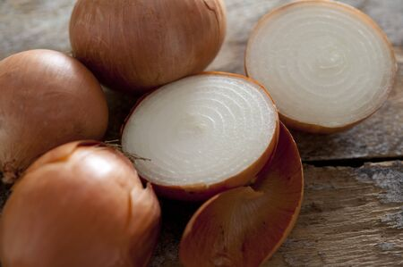 spanish onion: Close up of three whole and one halved fresh spanish onion with papery skin on a rustic wooden surface