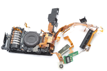 expose: One disassembled digital camera with exposed lens and green soldered board against a white background