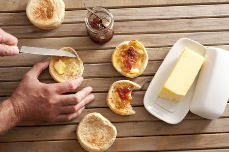 pat: Man buttering a freshly toasted crumpet for breakfast, overhead view of his hands, the crumpets, jam and a pat of farm butter on a slatted wooden table