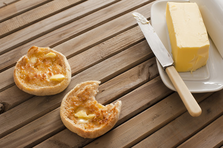 pat: Buttered crumpets for breakfast with a pat of butter alongside on a plate served on a wooden table, one crumpet bitten into