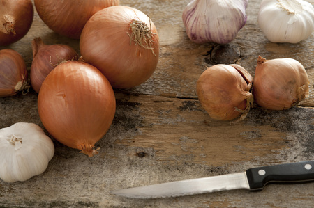 paring knife: Diverse selection of spanish onions and shallots next to three garlic bulbs on rustic table beside a paring knife