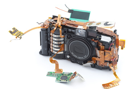 exposed: Disassembled digital camera with exposed copper ribbons attached to green soldered micro board