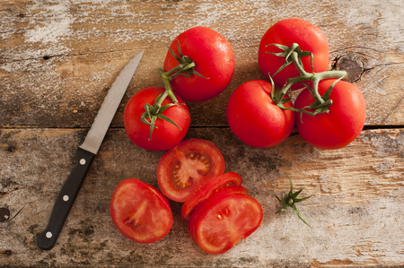 paring knife: Preparing sliced ripe red tomatoes on a rustic wooden kitchen counter with a paring knife, overhead view of sliced and whole tomatoes on the vine Stock Photo