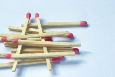 inflammable: Numerous new wooden match sticks stacked one upon the other over white background