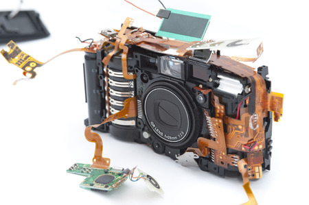 pulled over: Compact point and shoot camera with disassembled parts on pulled out circuit board and buttons over white background