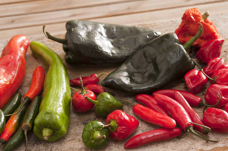 flavorings: Various long, short, red, green and black hot peppers scattered on cutting board outdoors over wooden table