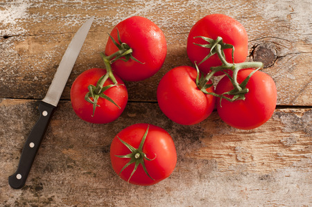 paring: Six vine ripe red tomatoes with stems and single black and metal paring knife over weathered wooden table