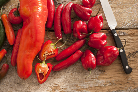 Small assortment of round and thin red hot peppers besides a stainless steel knife on a rustic table Stock Photo