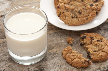 High Angle Close Up Still Life of Glass of Cold Refreshing Milk Beside Plate of Fresh Baked Cookies with Single Broken and Half Eaten Biscuit in Foreground Stock Photo