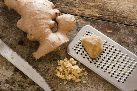 rasp: Freshly minced or grated root ginger on an old wooden kitchen table with a portion of whole root and a stainless steel grater or rasp Stock Photo