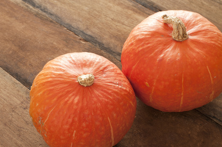 Two whole fresh orange autumn pumpkin or squash side by side on an old rustic wooden table, high angle view with copy space