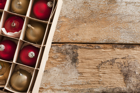 Box of packaged gold and red Christmas ornaments in neat compartments viewed from above on an old rustic wooden table with copy space for your seasonal greeting