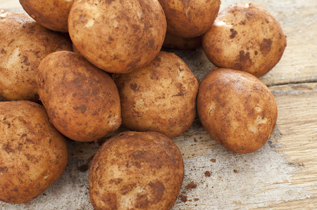 Freshly harvested whole fresh potatoes with adhering dirt in a pile at market on a rustic wooden table Stock Photo