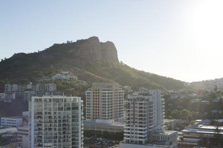 View of modern high-rise buildings in Townsville, Queensland overlooked by a mountain peak backlit by a hot summer sun in a travel concept