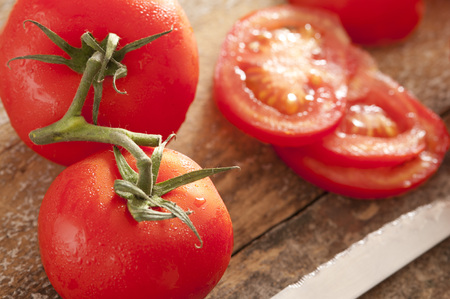 Fresh washed tomatoes with droplets of water on the vine and sliced ready for inclusion in a healthy summer salad on a wooden board with knife Stock Photo
