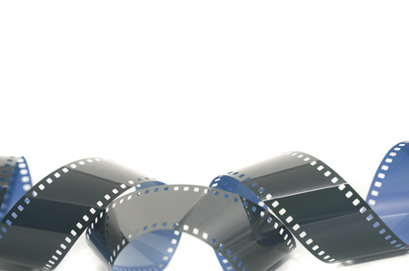 Coiled strip of 35mm photographic film unrolled and exposed forming a lower border over white with copy space Stock Photo