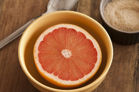 Cut fresh juicy pink grapefruit served for breakfast in a bowl with accompanying sugar for a healthy diet rich in vitamin C