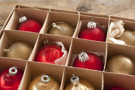 Cardboard box of colorful Christmas decorations with red and gold baubles or balls for the Xmas tree to celebrate the festive holiday season Stock Photo