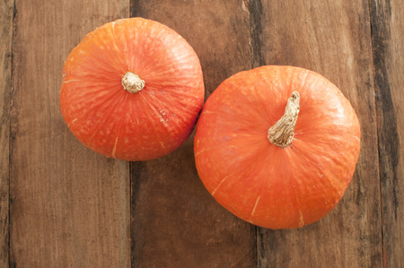 Top down view on small orange pumpkins over wooden background for concept about autumn season produce or Halloween