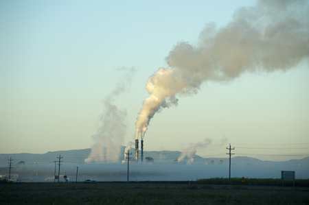 View of sugar processing plant behind fog or low clouds with stream piping up through smokestacks