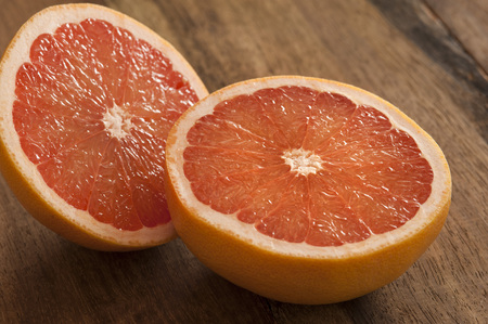 Close up view on fresh raw single pink grapefruit cut in half over dark wooden table