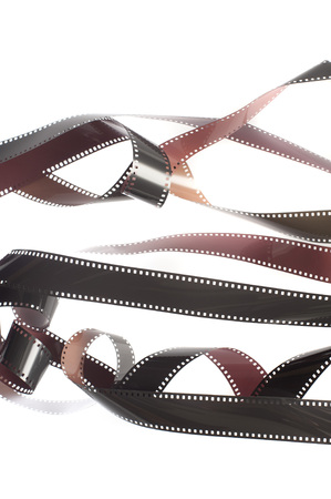 Rolls of unrolled and tangled 35mm film strips stretched out over white background