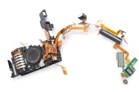 Dismantled camera lying in parts on white with the components spread out in an arc forming a border with copy space