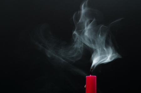A red candle is smoking photo