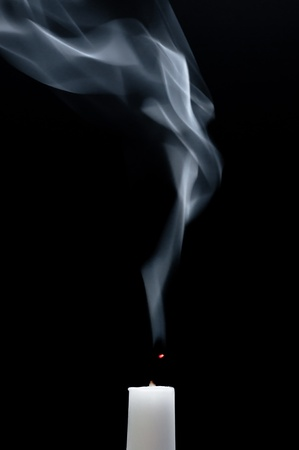 A white candle is smoking after it is extinguished photo