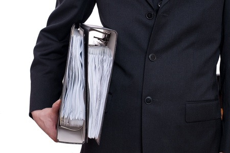 A man in a suit is holding two files under his arm