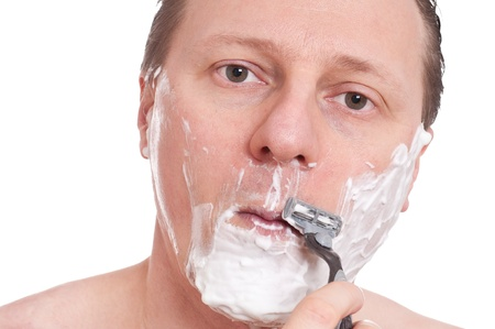 A caucasian with shaving foam in his face is shaving with a razor