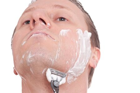 A man is shaving his face with a razor photo