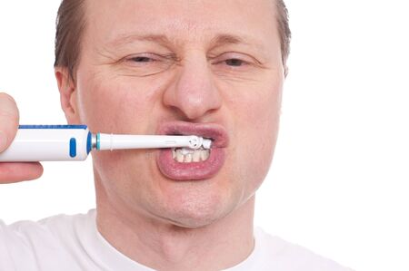teeths: Caucasian is cleaning his teeths with a electric toothbrush