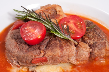 Stewed ossobuco with tomatoes and rosemary and mashed potatoes and tomato sauce photo