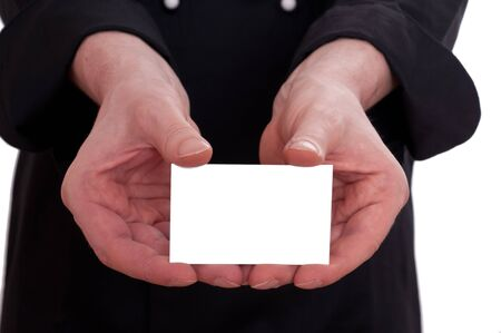 Cook is holding a blank business card in has hand between his fingers photo