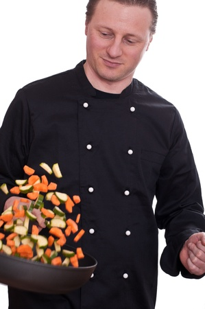 A cook is turning the carrots and courgettes in a pan Stock Photo - 12533704