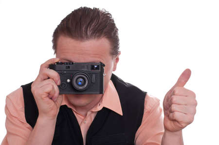 A male photographer is holding a camera in his hands und holding up his thumb photo