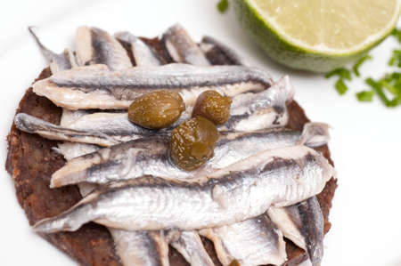 pumpernickel: Canape with Pumpernickel and sardines and capers Stock Photo