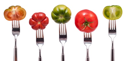 Display with five isolated different green and red tomatoes photo