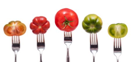 Isolated five tomatoes in red and green on a fork photo