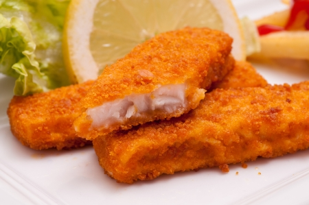 Fast food with three breaded fish fingers and a slice of lemon photo